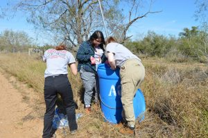Sammi, Tanya, and Sidney replenishing a water station.