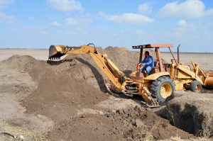 Joe filling our pit with dirt, using the back hoe